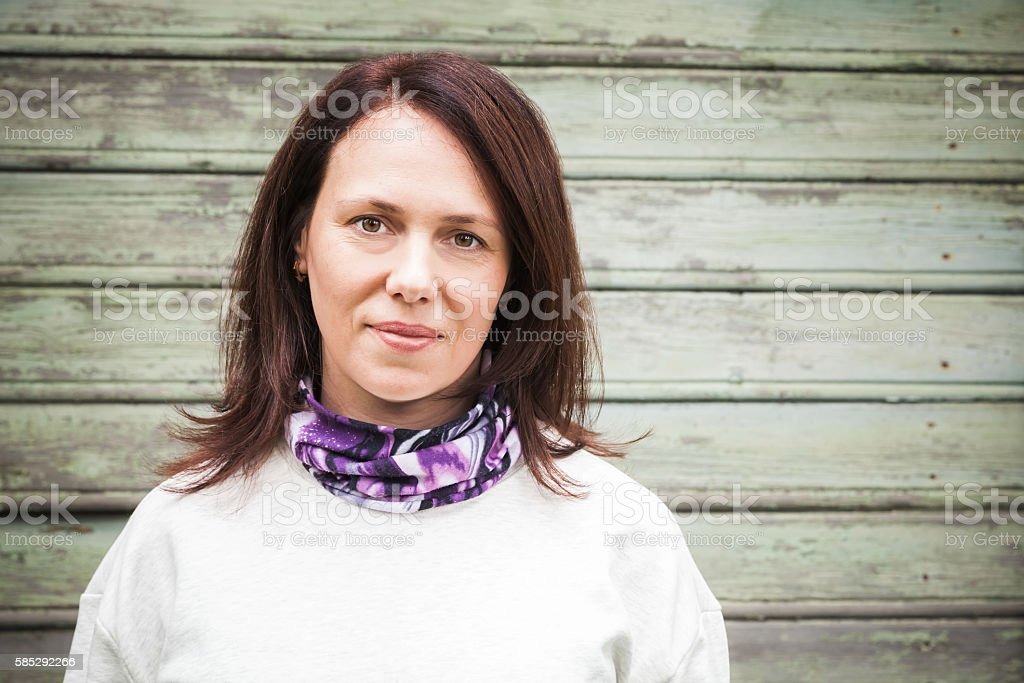 Young Caucasian woman over green wall stock photo