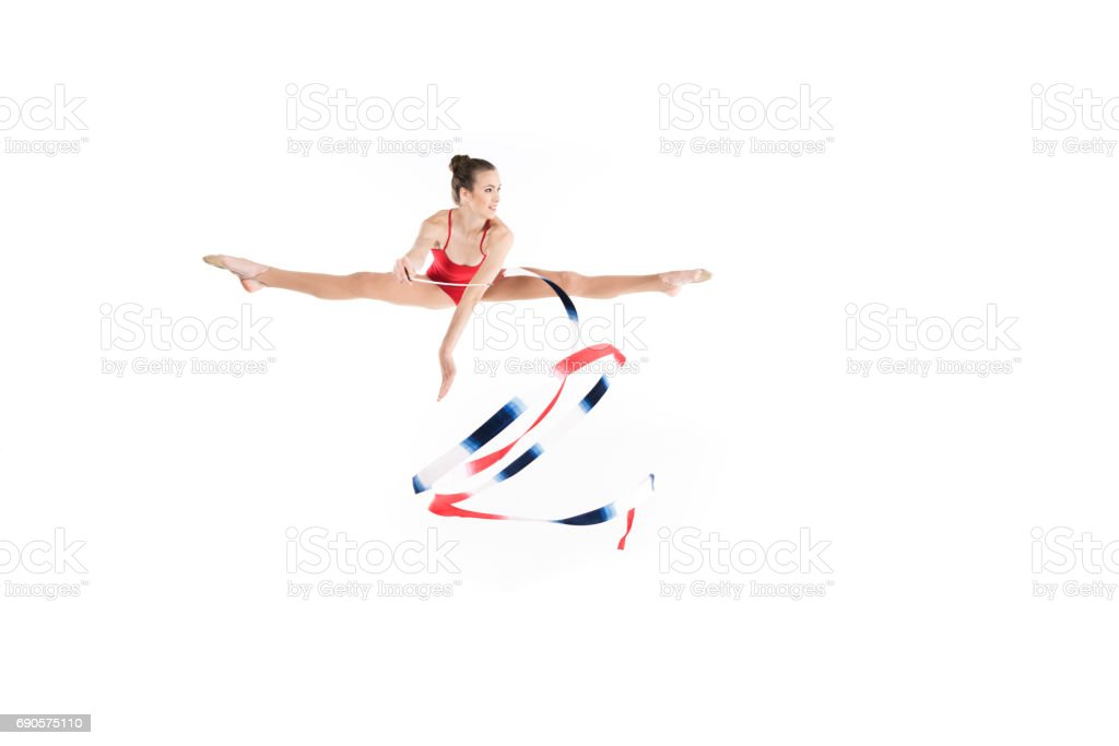 young caucasian woman rhythmic gymnast jumping with colorful rope stock photo