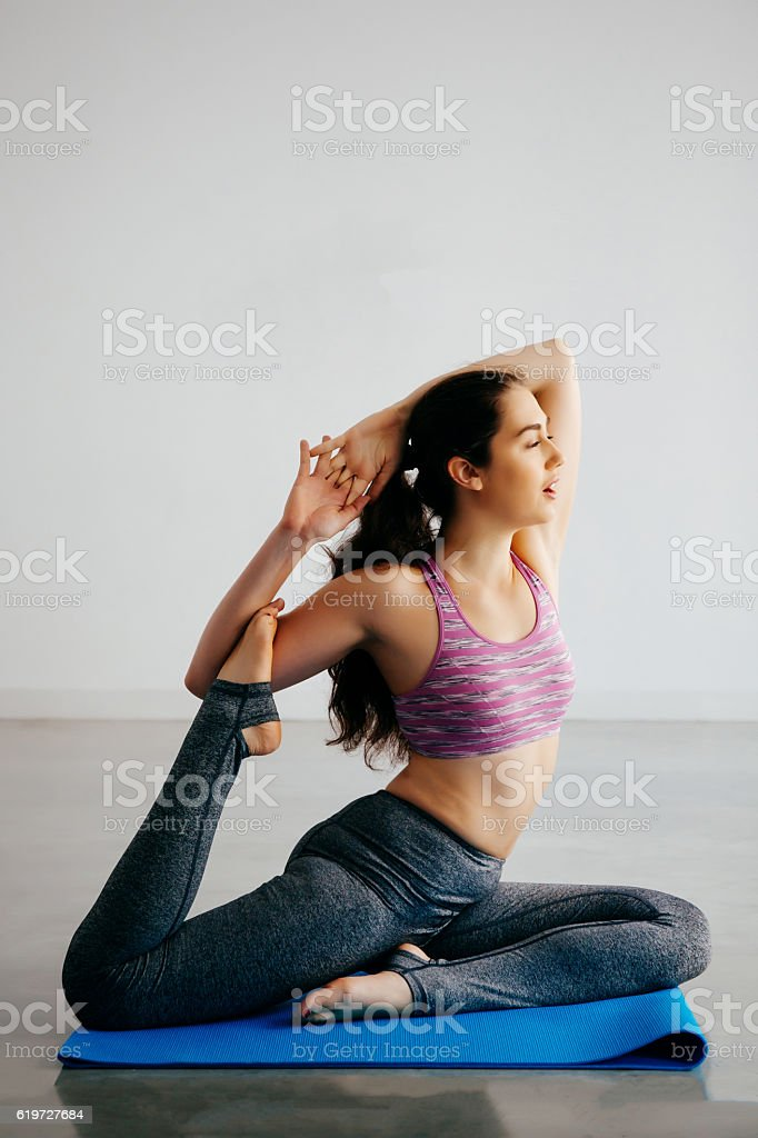 Young Caucasian woman stretching and doing yoga with copy space stock photo