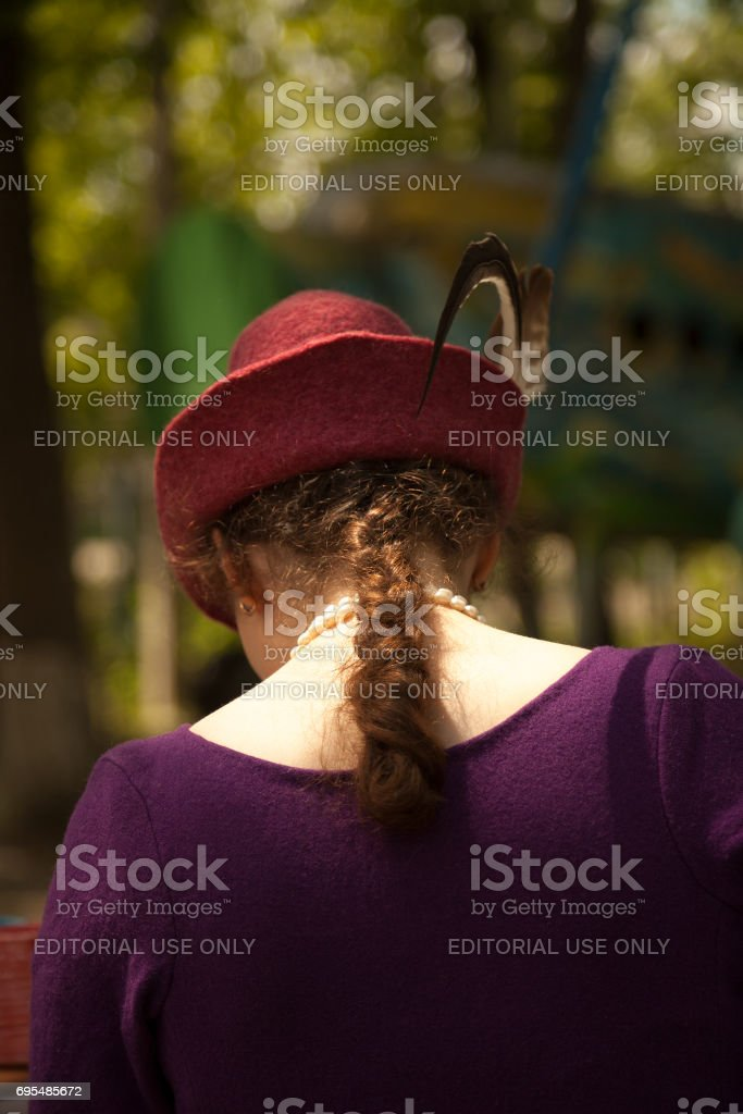 Young Caucasian woman wearing historical costume - felt purple dress and red Tirol hat with feathers stock photo