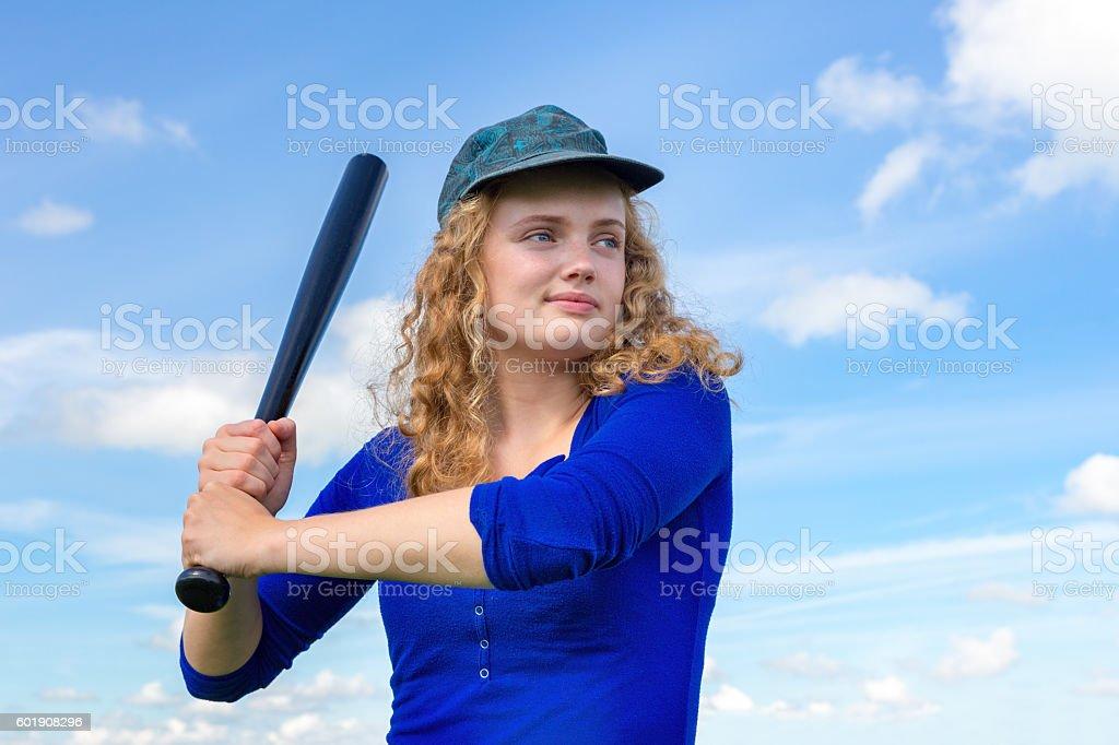 Young caucasian woman with baseball bat and cap stock photo