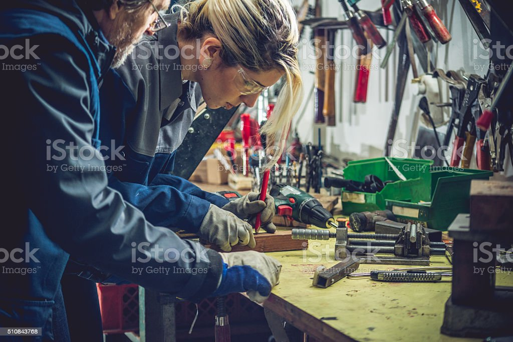 Young Caucasian Woman Working in Garage or Mechanical Workshop stock photo