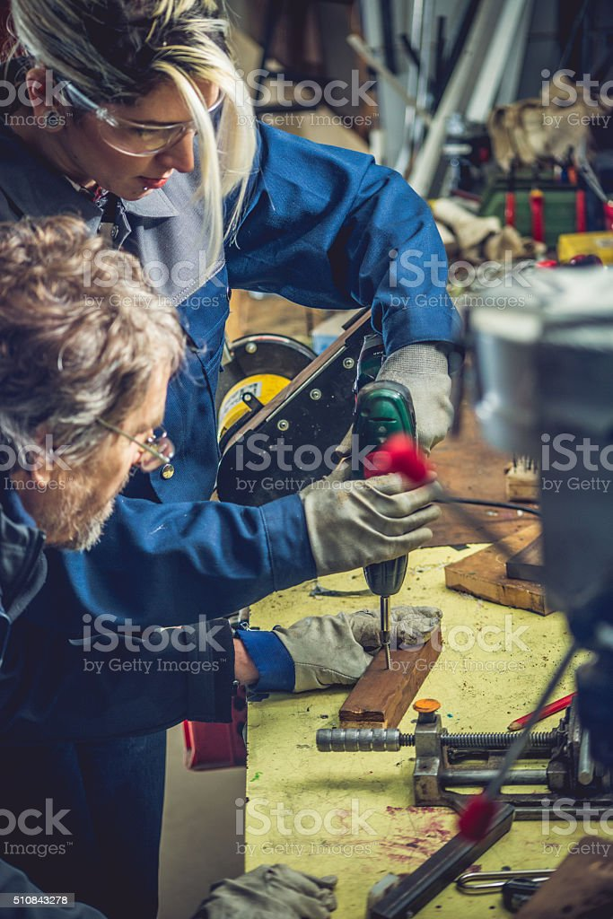 Young Caucasian Woman Working in Garage Using Electric Screwdriver stock photo
