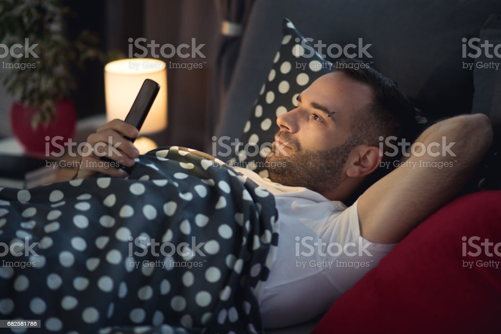 Young cell phone addict man in bed using smartphone stock photo