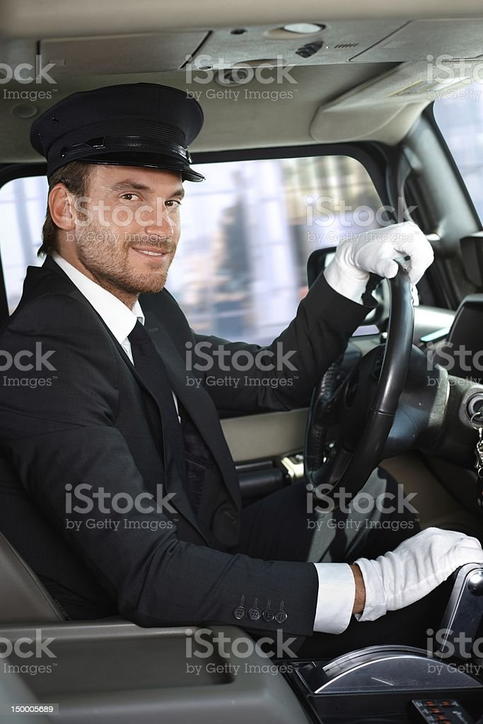 Young chauffeur in limousine smiling stock photo