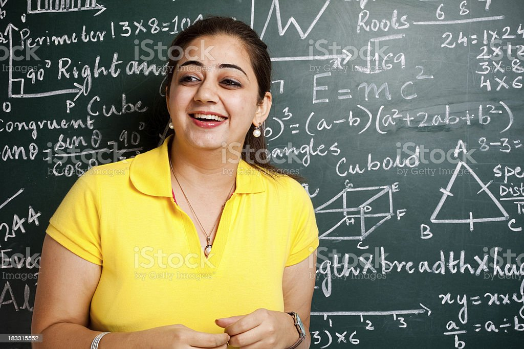 Young Cheerful Attractive Female Indian Teacher in Classroom with Greenboard royalty-free stock photo