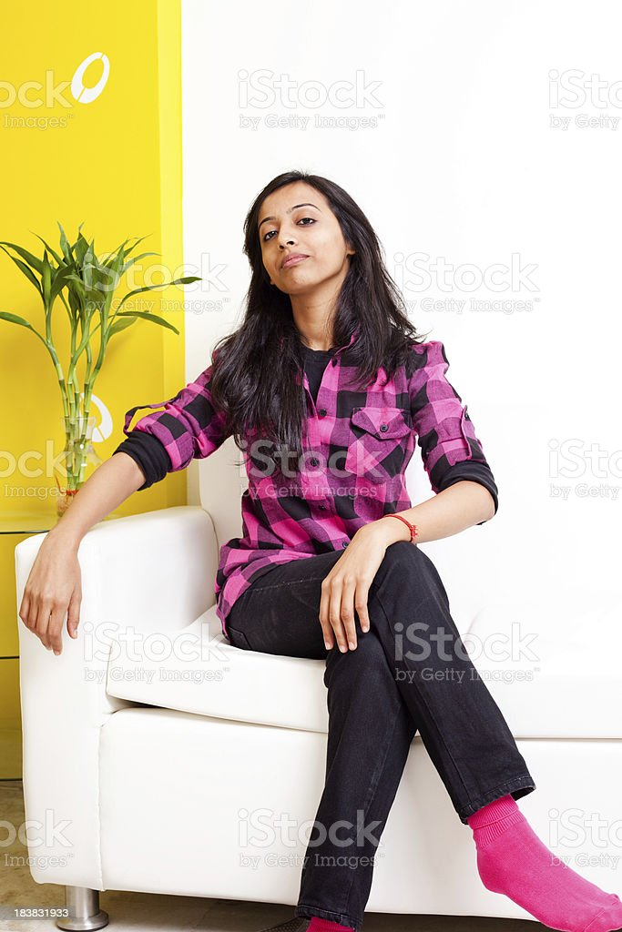Young Cheerful Attractive Indian Adult Female Sitting on a Couch royalty-free stock photo
