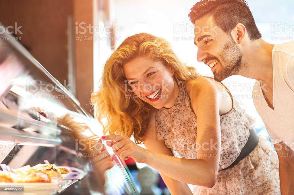 Young cheerful couple buying sweets stock photo