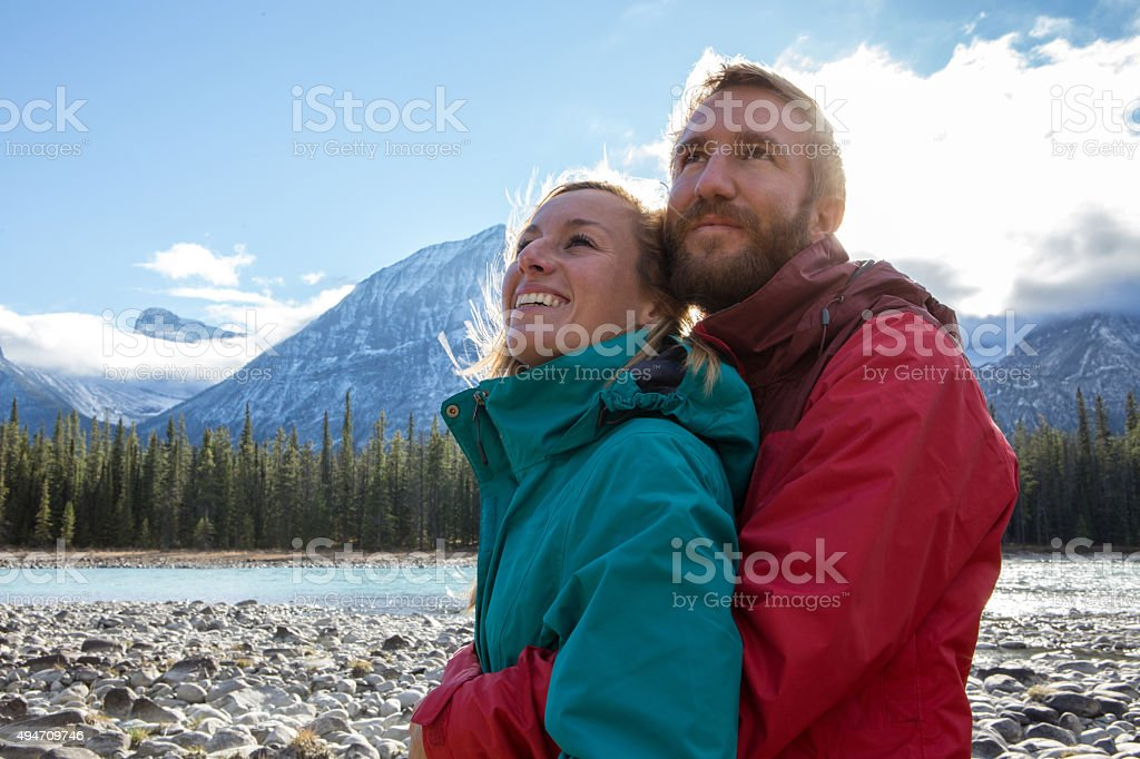 Young cheerful couple by the river being affectionate stock photo