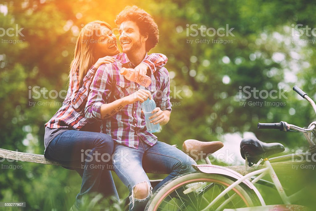 Young Cheerful Couple Drinking Water After Riding Bicycles. stock photo