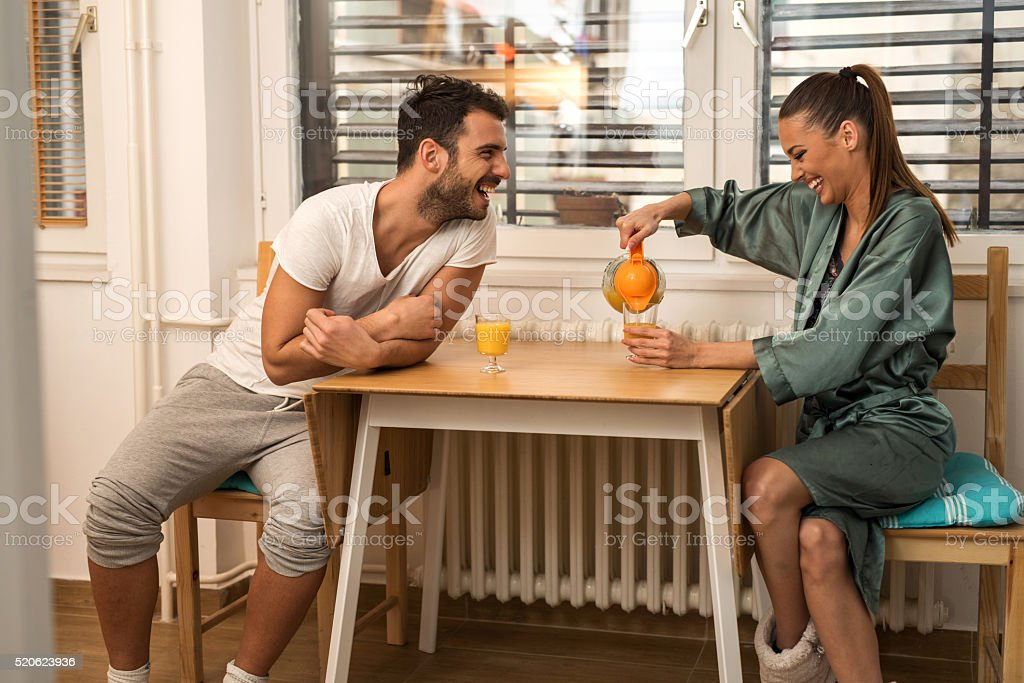 Young cheerful couple having an orange juice in the morning. stock photo
