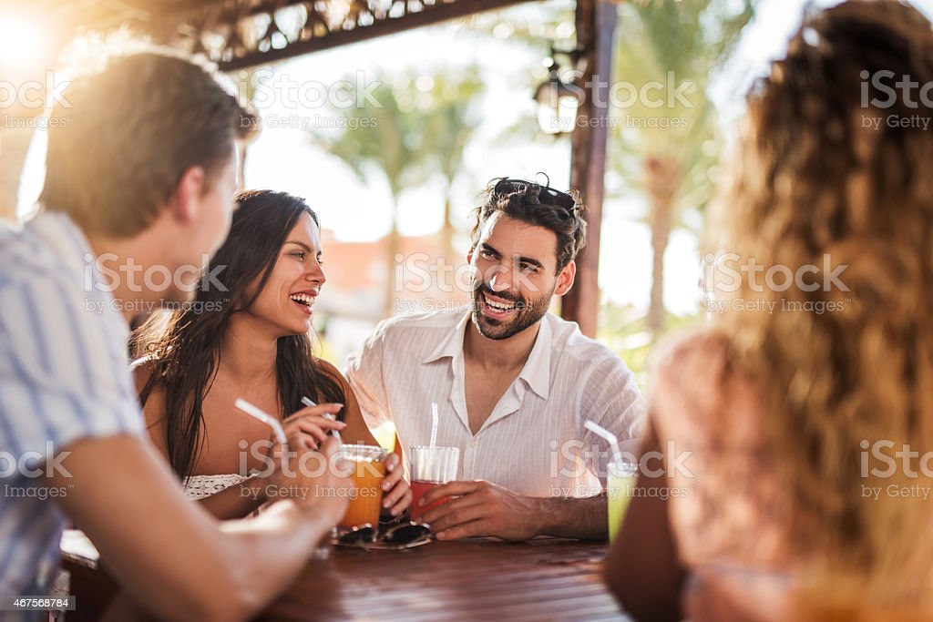 Young cheerful couple having fun with their friends in bar. stock photo