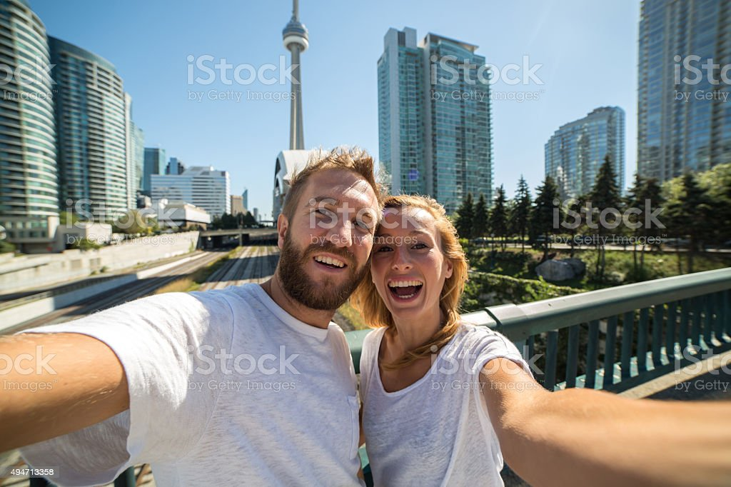 Young cheerful couple in Toronto taking selfie portrait with cityscape stock photo