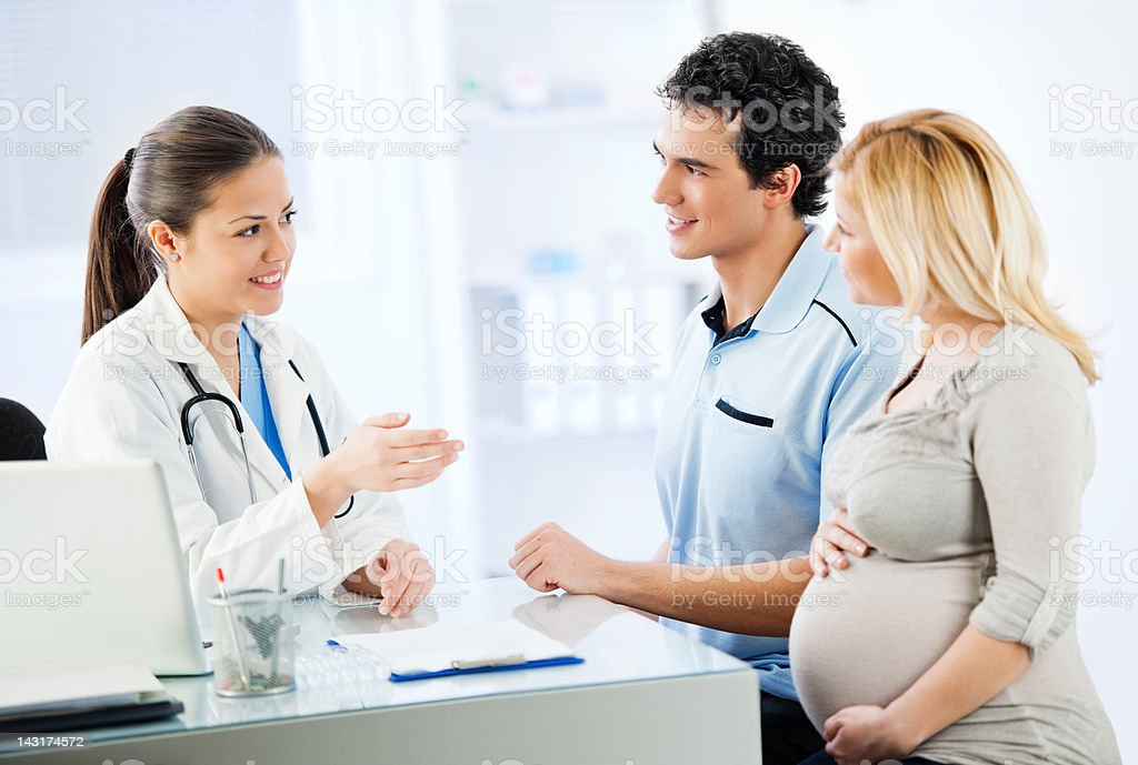 Young cheerful couple visiting a doctor royalty-free stock photo