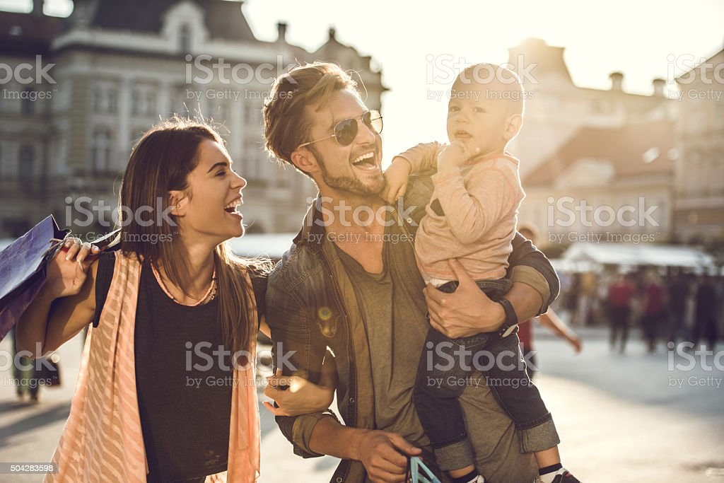 Young cheerful family enjoying in shopping day at the city. stock photo