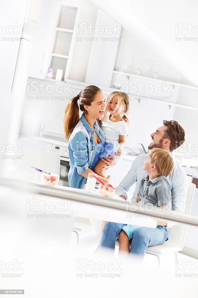 Young cheerful family having fun in the kitchen. stock photo