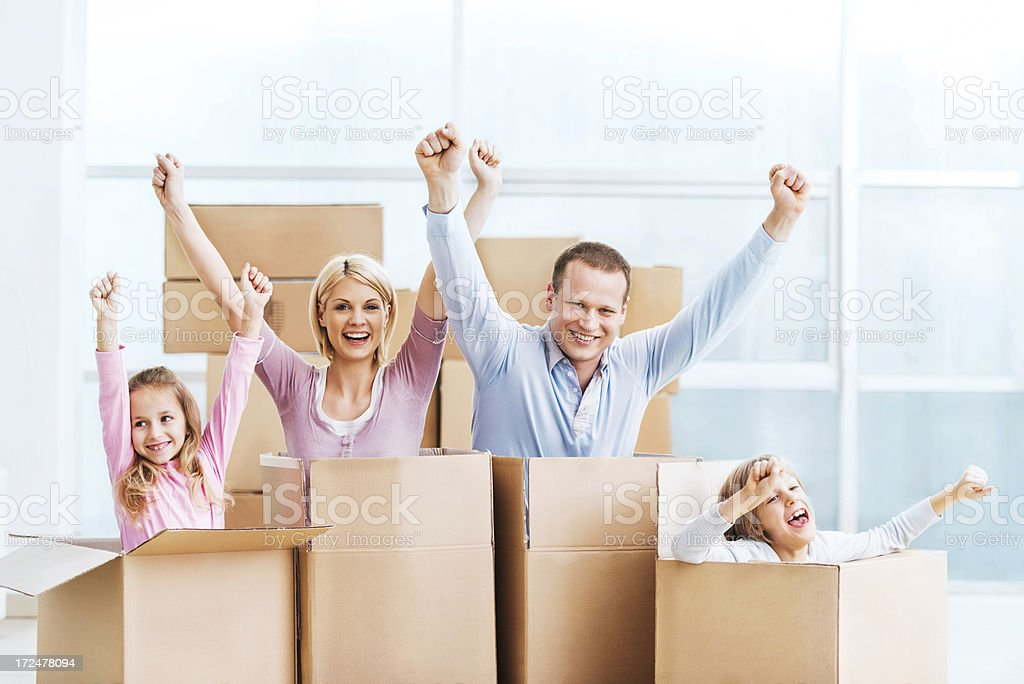 Young cheerful family in cardboard boxes. stock photo