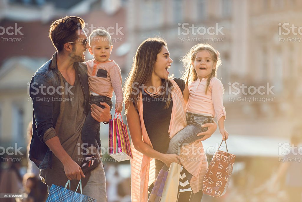 Young cheerful family shopping together in the city. stock photo