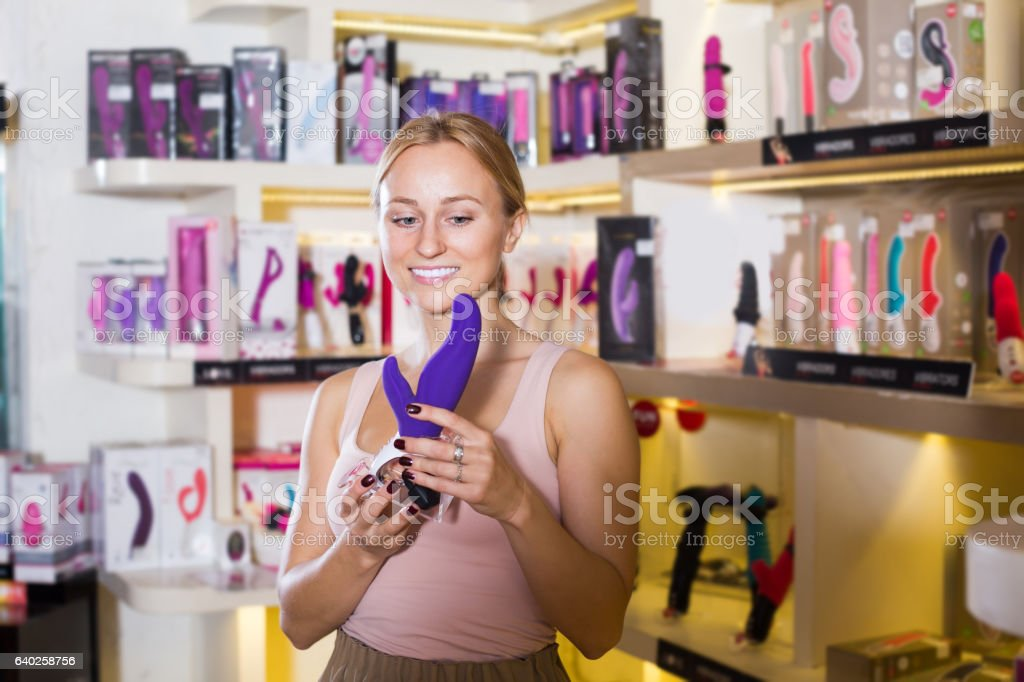 Young cheerful female buying sex toys in shop stock photo