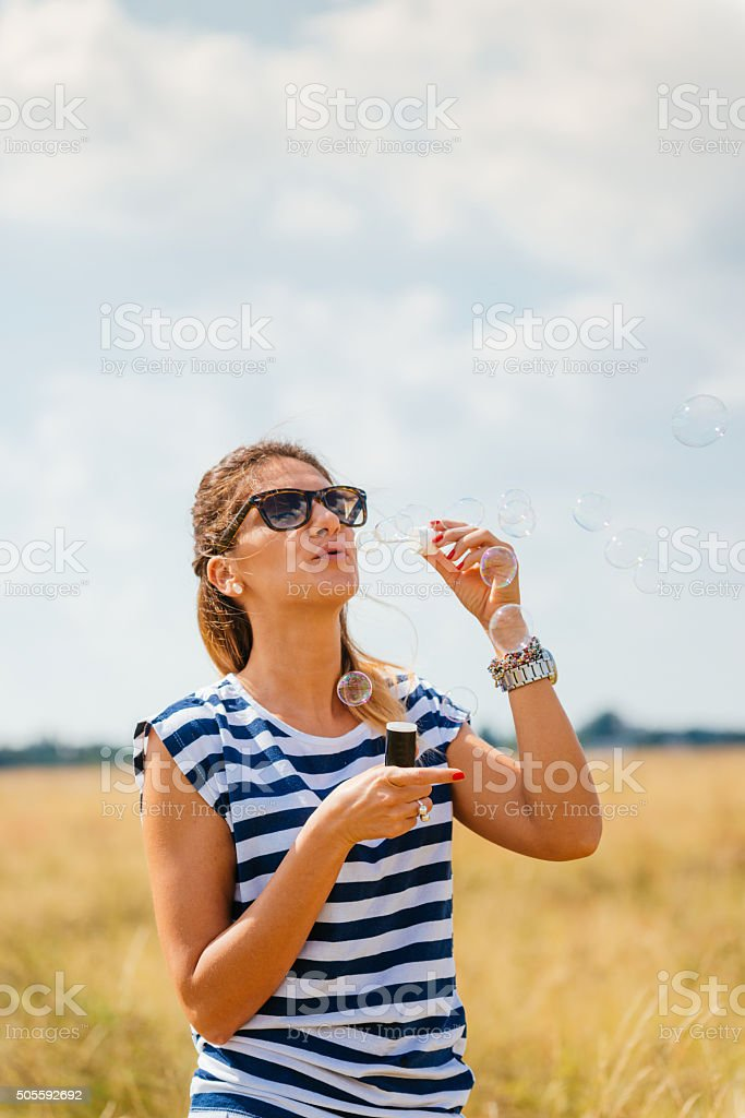 Young cheerful girl blowing bubbles in park in summer stock photo