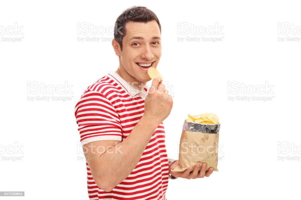 Young cheerful guy eating potato chips stock photo