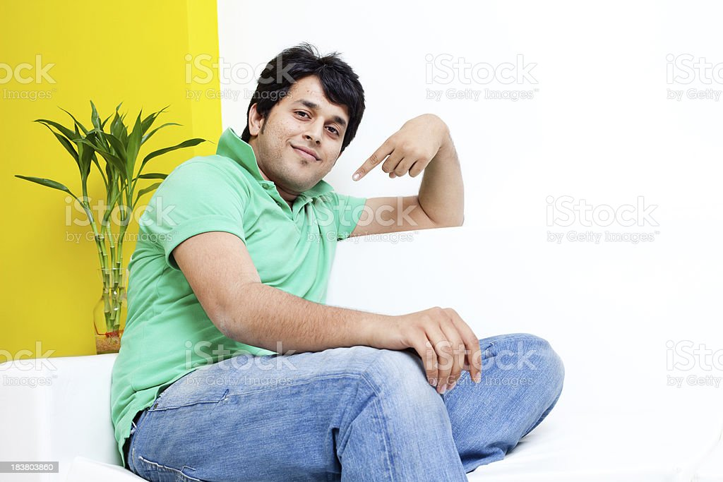 Young Cheerful Handsome Indian Adult male Sitting on a Couch royalty-free stock photo