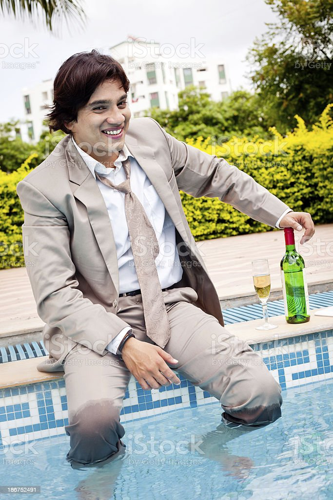 Young cheerful Indian businessman relaxing at swimming pool side royalty-free stock photo