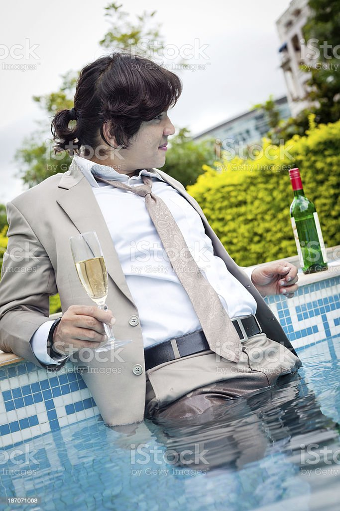 Young cheerful Indian businessman relaxing at swimming poolside royalty-free stock photo