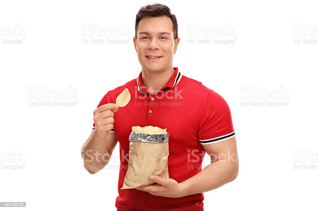 Young cheerful man eating potato chips stock photo