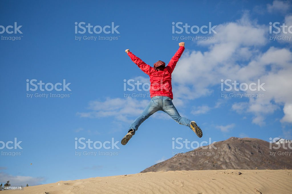 Young cheerful man in desert jumping makes cross shape stock photo