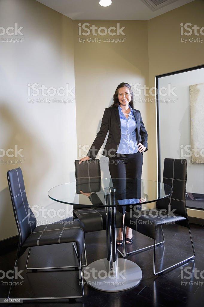Joven Alegre Empleada de oficina independiente de la mesa redonda de vidrio foto de stock libre de derechos
