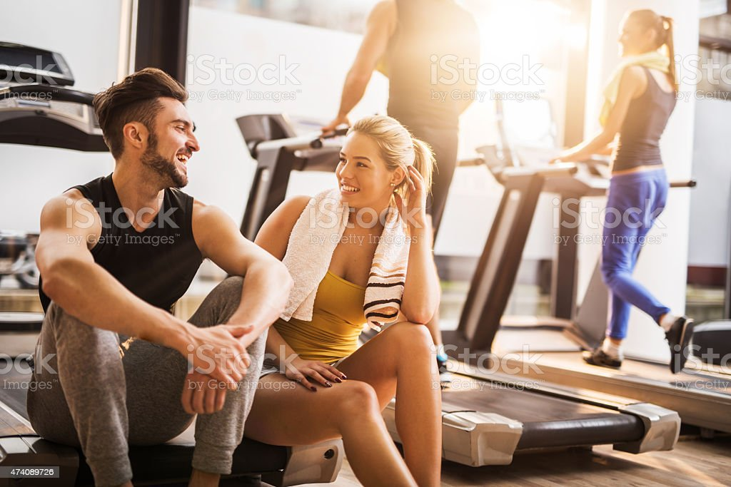Young cheerful people resting from exercising at gym and communicating. stock photo