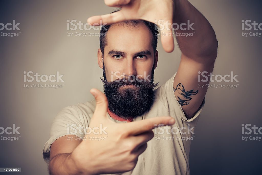 Young cheerful photographer with beard, while working in studio stock photo