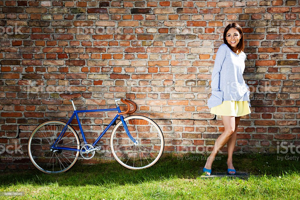 Young cheerful woman and old blue bike stock photo