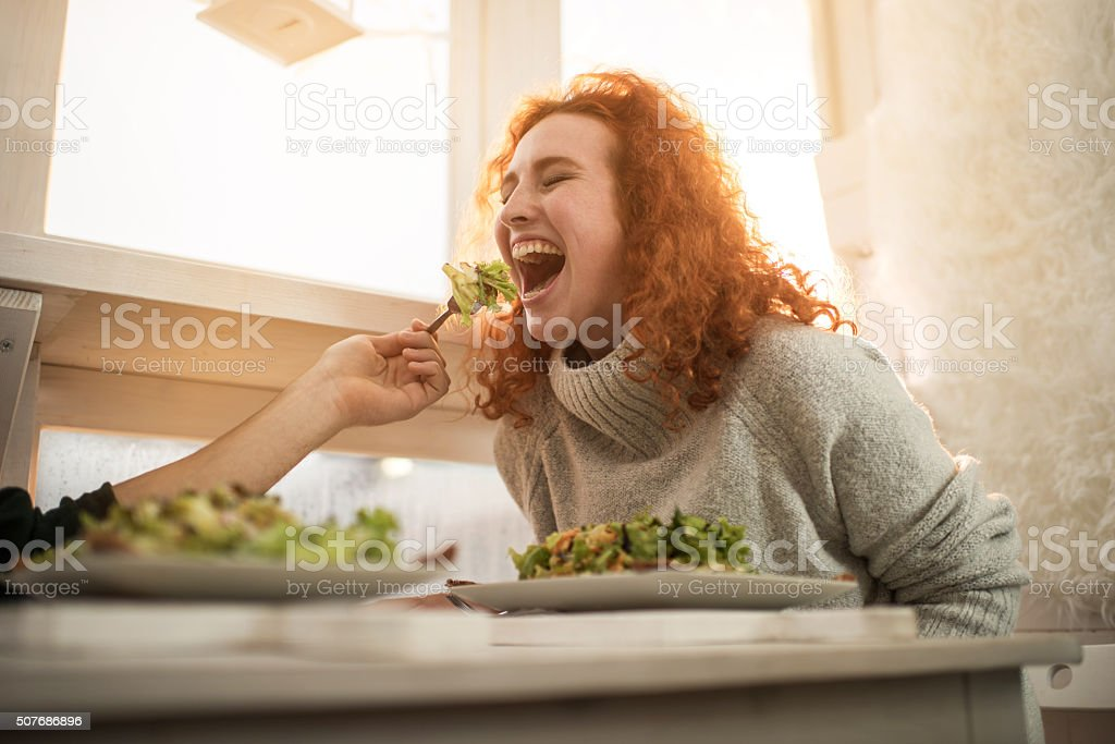 Young cheerful woman being fed by unrecognizable man. stock photo