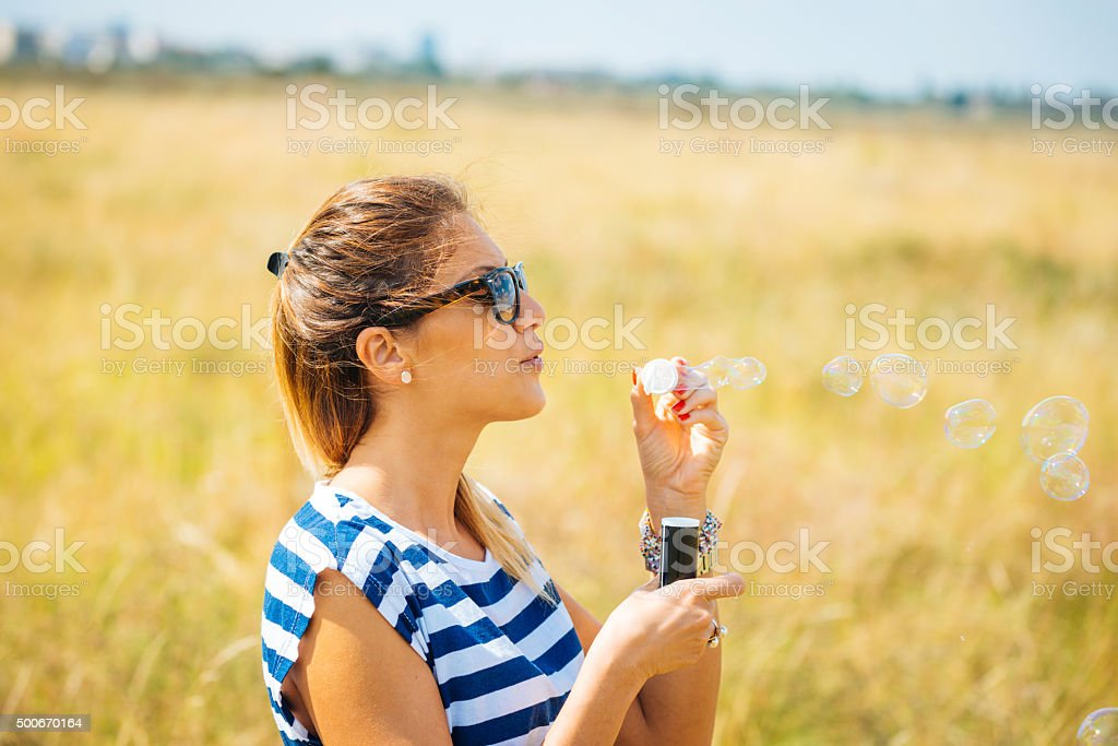 Young cheerful woman blowing bubbles in park in summer stock photo
