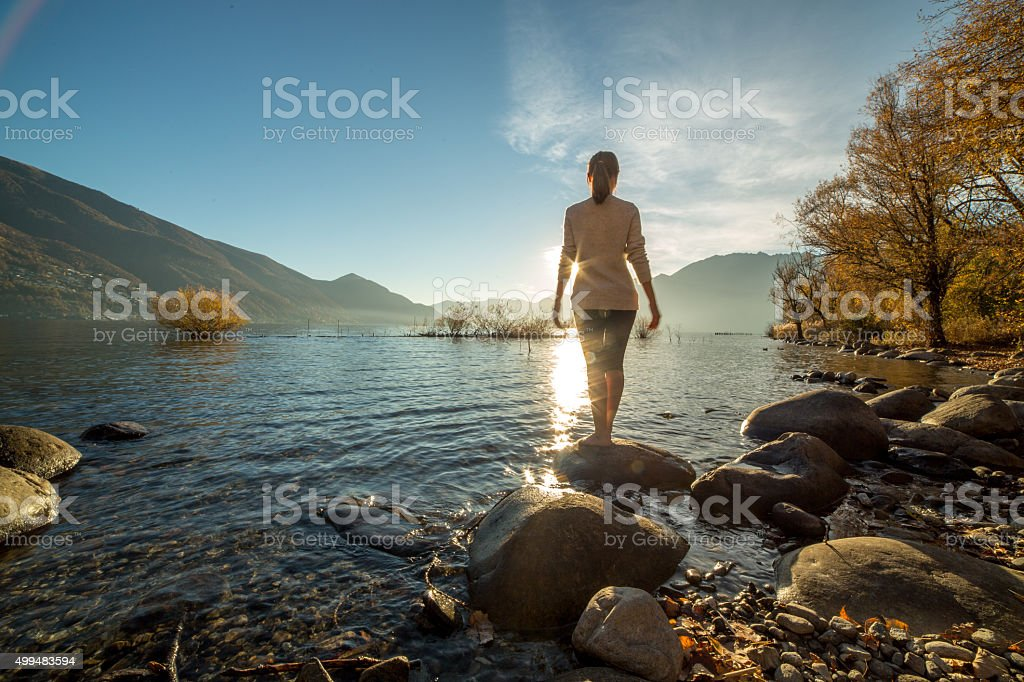 Young cheerful woman by the lake at sunset enjoying nature stock photo