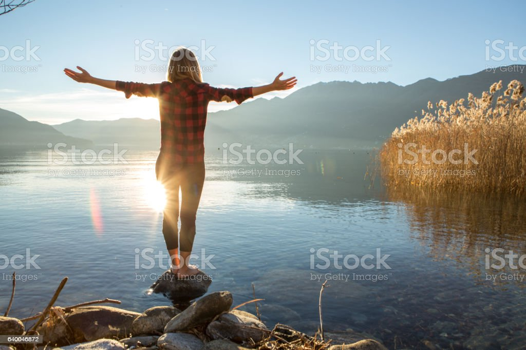 Young cheerful woman by the lake enjoying nature stock photo