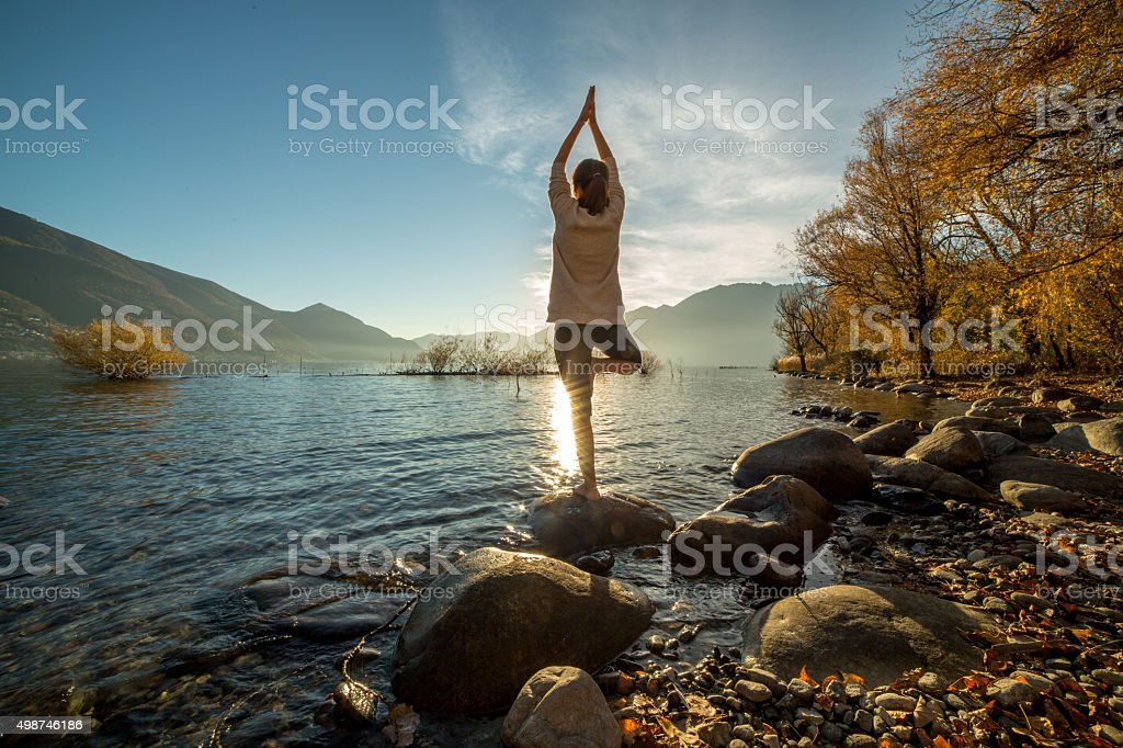 Young cheerful woman by the lake exercising yoga at sunset stock photo