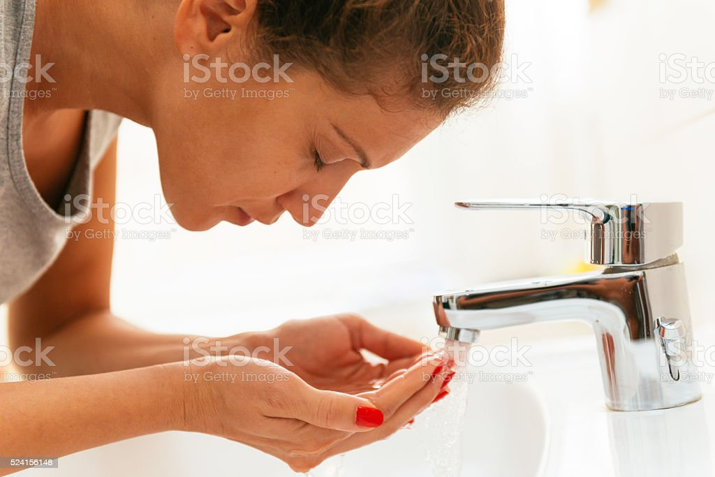 Young cheerful woman having morning hygiene in bathroom stock photo