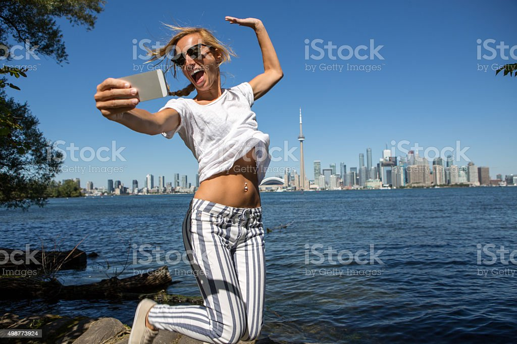 Young cheerful woman in Toronto-Canada taking a selfie portrait stock photo