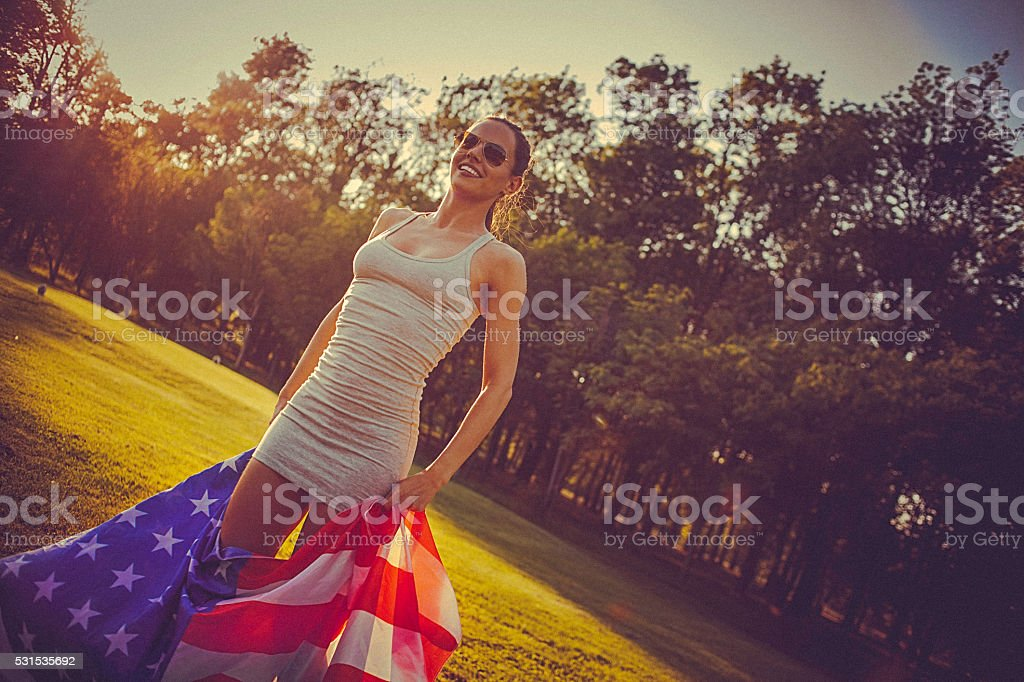 Young cheerful woman standing in a meadow holding american flag stock photo