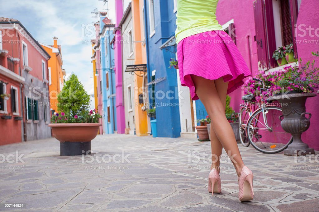 Young cheerful woman walking in streets of old town stock photo