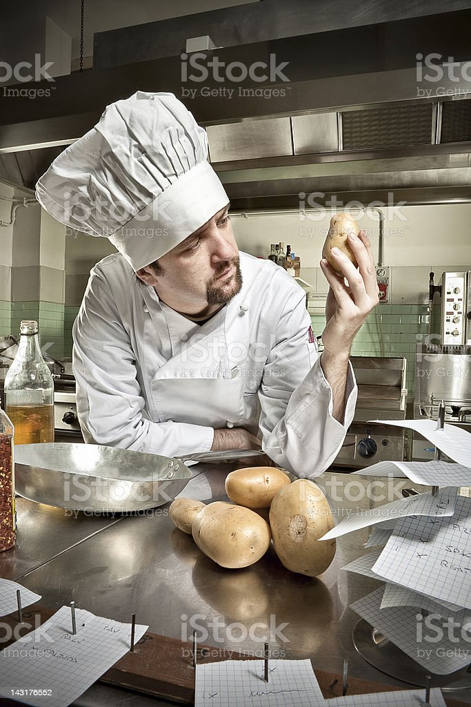 Young chef contemplating potato royalty-free stock photo