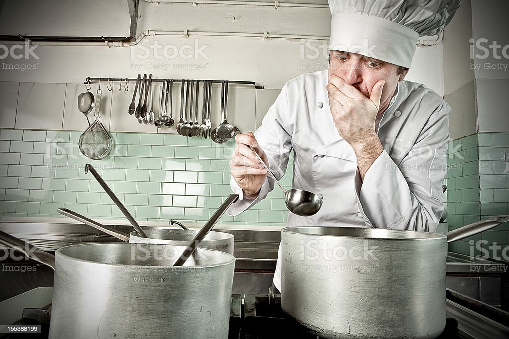 Young chef tasting soup stock photo