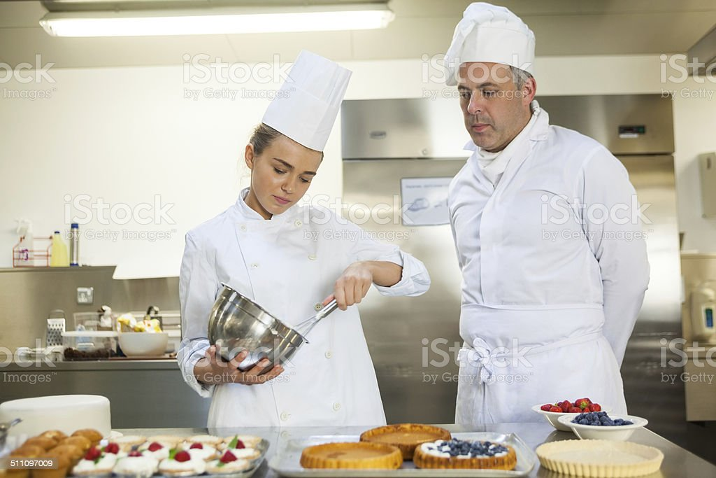 Young chef whisking while being watched stock photo