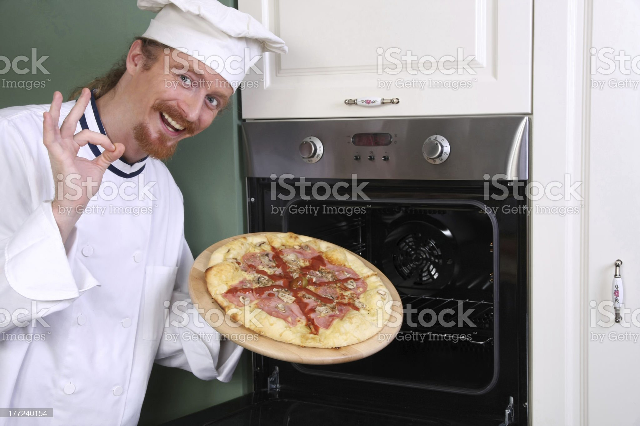 young chef with italian pizza in kitchen royalty-free stock photo