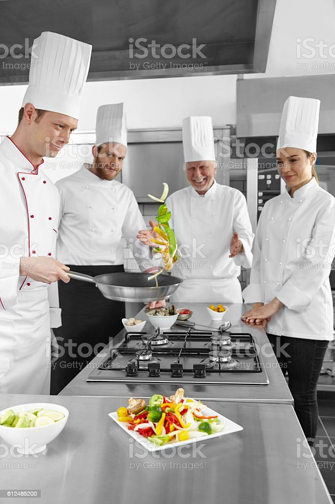 Young chefs cooking vegetable in pan. stock photo