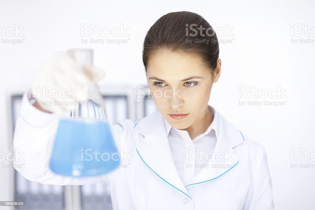 Young chemical female researcher holding flask in laboratory royalty-free stock photo