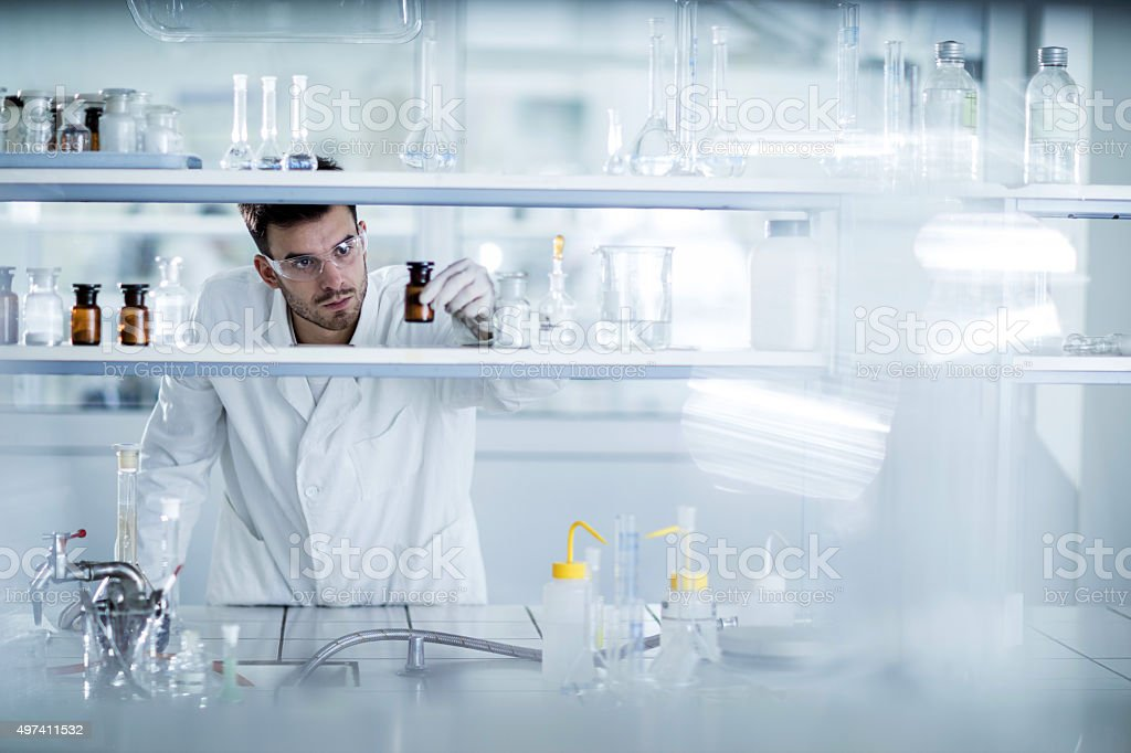 Young chemist choosing the right bottle in a laboratory. stock photo